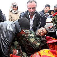 A rebel fighter severly injured by an explosion during clashes with government troops is taken from a car outside of Ajdabiya, 100 miles south of Benghazi, Libya. March 2011.