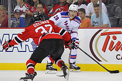 Sep 16, 2013; Newark, NJ, USA; New York Rangers left wing Chris Kreider (20) skates with the puck while being defended by New Jersey Devils defenseman Eric Gelinas (32) during the first period at Prudential Center.