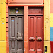 """Orange and gray painted wood double doors in San Telmo barrio, the heart of old Buenos Aires, Argentina, South America. Admire well-preserved old buildings in San Telmo (""""Saint Pedro González Telmo""""), the oldest barrio (neighborhood) of Buenos Aires, in Argentina, South America."""