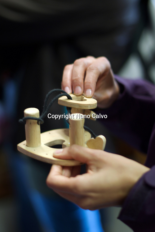Wooden puzzle games. Traditional costumes and folk traditions at Easter Festival in Hollókő, UNESCO World Heritage-listed village in the Cserhát Hills of the Northern Uplands, Hungary.