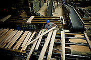 Bryce Brumley straightens out lumber on a conveyor belt at the Sierra Pacific lumber mill in Chinese Camp, Calif., July 25, 2012..CREDIT: Max Whittaker/Prime for The Wall Street Journal.TIMBER