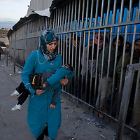 A Palestinian woman carries her sleepy child  along the separation wall at the checkpoint 300, the crossing passage between Bethleem and Jerusalem, on December 15. 2010 in Bethleem. Workers arrived every day at two o'clock in the morning  to catch a place at the entrance of the checkpoint, so they can arrived at time to their work in the Israeli side. Photo by Olivier Fitoussi