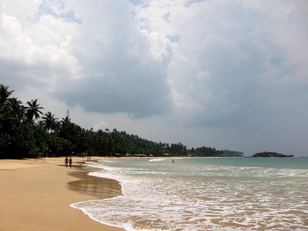 A couple walks along Mirissa Beach in southern Sri Lanka