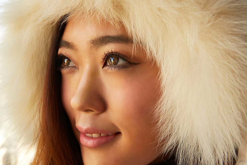 Portrait of an inspired Japanese girl who is wearing a fur hood during winter