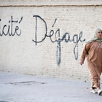 USE ARROWS &larr; &rarr; on your keyboard to navigate this slide-show<br /> <br /> Kairouan, Tunisia, 27 October 2011<br /> A Tunisian woman walks in front of a graffiti against secularism.<br /> Photo: Ezequiel Scagnetti