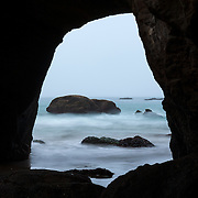 Crashing Pacific Ocean waves are visible through the Devils Punch Bowl Arch on the central Oregon coast. Devils Punch Bowl is a large, natural bowl in the bluff along the coast and is believed to be the remnant of two collapsed sea caves.