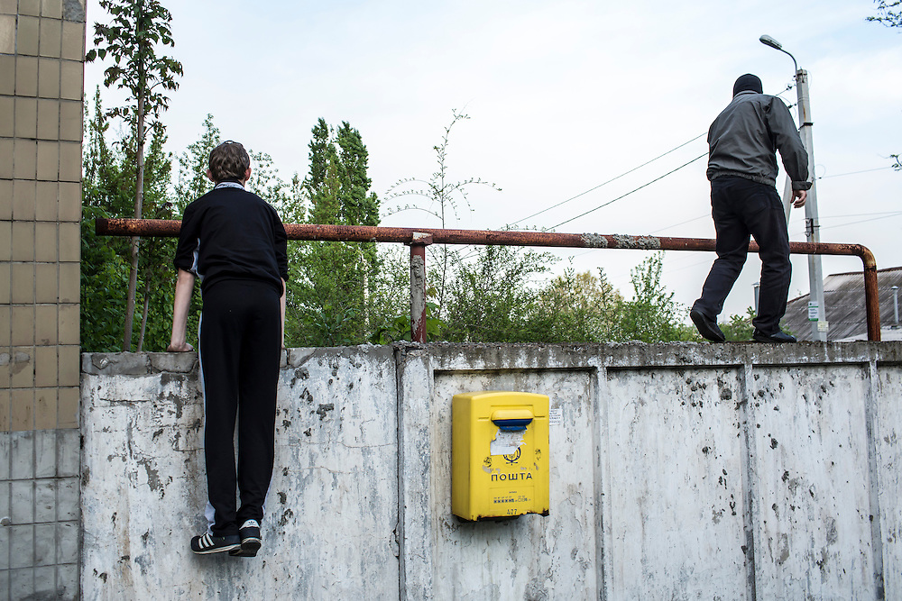 DONETSK, UKRAINE - MAY 4: Pro-Russian protesters climb a wall while trying to enter and occupy the military prosecutor's office on May 4, 2014 in Donetsk, Ukraine. Cities across Eastern Ukraine have been overtaken by pro-Russian protesters in recent weeks, leading the Ukrainian military to respond with force in some areas. (Photo by Brendan Hoffman for The Washington Post)