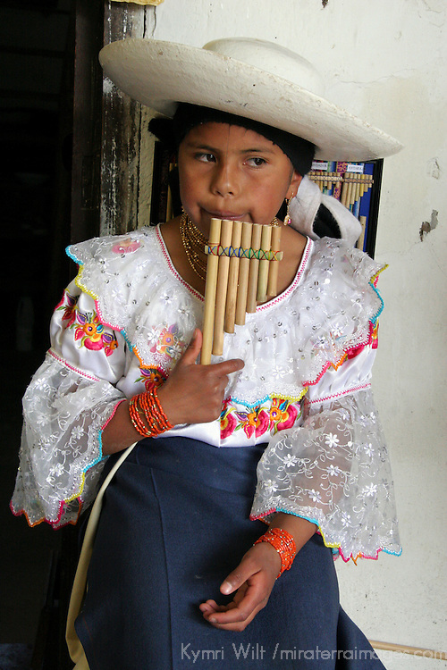 South America, Ecuador, Peguche. A young Ecuadorian girl plays the panflute, a traditonal instrument of the Andes.