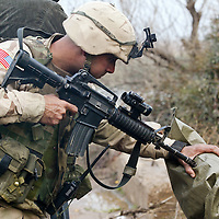 A U.S. soldier from the Fourth Infantry Division points his rifle to the head of a suspected insurgent while questioning him in Asaki, Iraq, 50 miles north of Baghdad. More than 70 suspected insurgents were arrested in this roundup, after a large weapons and explosives cache was uncovered in a nearby field. December 2003.