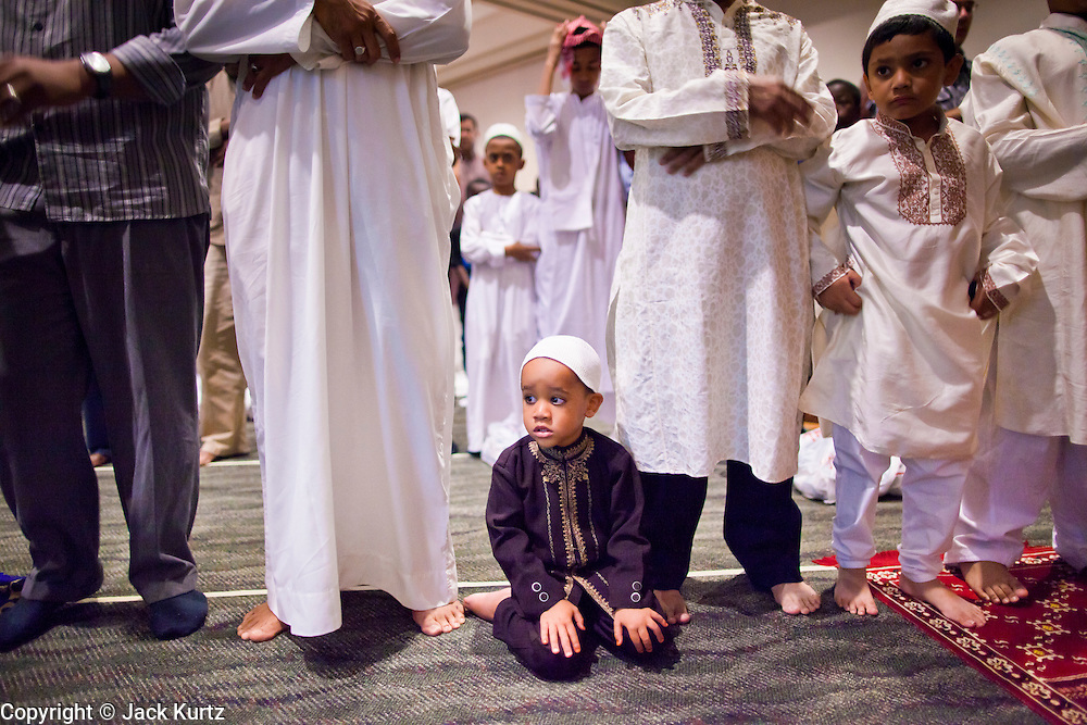 """Sept. 10 - GLENDALE, AZ: Muslim men pray during Eid ul-Fitr services in the Glendale Civic Center. More than 3,000 Muslims from the Phoenix area celebrated Eid ul-Fitr, the end of Ramadan, at the Glendale Civic Center in Glendale, AZ, a suburb of Phoenix. Eid ul-Fitr, often abbreviated to Eid, is the Muslim holiday that marks the end of Ramadan, the Islamic holy month of fasting. Eid is an Arabic word meaning """"festivity"""", while Fitr means """"conclusion of the fast""""; and so the holiday symbolizes the celebration of the conclusion of the month of fasting from dawn to sunset during the entire month of Ramadan. The first day of Eid, therefore, is the first day of the month Shawwal that comes after Ramadan.  Photo by Jack Kurtz"""