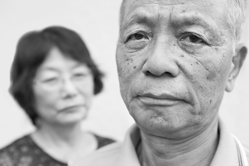 Black and white portrait photograph of Oriental senior man living in fear with wife looking at him in background