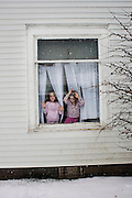 Kacey and Lacey Sellers, 5, stand in the window of their family's home in Chauncey, Ohio on January 21, 2007. The identical twins were both born deaf.