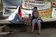 Nestor Reyes, 31, lays on the lap of his wife Sandra Morales, 30, while their one-year old son Emilio also takes a break. All three, from the hamlet of El Carrizal, continually participate in the La Puya resistance blockade. Since March 2nd, 2012, local neighbors from San José del Golfo and San Pedro Ayampuc have blocked the entrance to the EXMINGUA gold mine - owned by Kappes, Cassiday & Assocaites (KCA) based in Reno, Nevada, USA. Residents from the communities claim the industrial activity in their territories as illegal since they were not appropriately consulted before the mine began operating. La Puya, San Pedro Ayampuc, Guatemala. May 14, 2013.