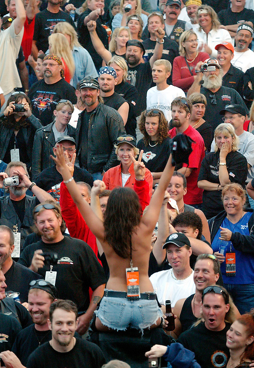 A topless woman waves at the Harley-Davidson closing party in downtown Milwaukee August 31, 2003.  The legendary American motorcycle company celebrated its 100th anniversary over four days.  REUTERS/Allen Fredrickson