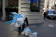 A workman struggles to pick up dropped packaging (including bubble wrap) in the City of London, the capital's financial district also known as the Square Mile, on 6th April 2017, in London, England.
