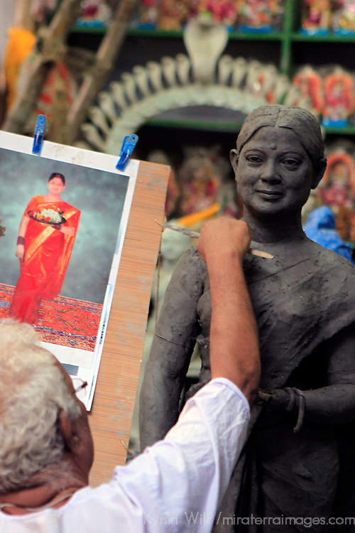 Asia, India, Calcutta. Clay artist sculpts from a photograph in the potter's village of Kumartuli in Calcutta.