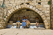 These four children rested on the arch covered  bench. The child on the left, being an orthodox Jew hid his face when he saw the camera. Zefat, Israel.