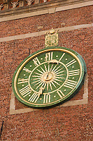wawel cathedral clock face seen in soft afternoon sunlight. surrounding brickwork and motifs form interesting architectural setting