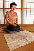 "Ms HIROKO KATAKEYAMA. Hiroshima A-Bomb survivor, siting in front of an old map showing the epicenter and the range or the A-bomb in the city of Hiroshima. Elementary school student who was four kilometers from the epicenter.  She lost many of her relatives in the bombing, including her cousin who was the same age.  We felt worn our and usually retreated to the barn, away from the quarreling adults.  One day my cousin confessed that his hair had started falling out.  I still vividly remember his blank face, frightened at this sign of death.  She still cries when she tells this story and is one of the few survivors who confesses to hating America. When she was invited by the UN to speak in New York two years ago, she almost didn't go. ""I couldn't bear the thought of going to the US""."