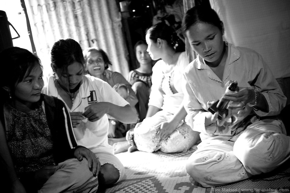 """Srey Leat, a prostitute living in a slum where """"Acting for Women in Distressing Situations"""" (AFESIP) conducts outreach and provides services, practices condom application during an AFESIP talk in Phnom Penh, Cambodia. Srey Leat, 24, has been a prostitute for three years. She arrived in Phnom Penh as a victim of sex trafficking. The slum's permanent structure, a decaying four story building known simply as 'The Building', was built in the 1960's as transitional housing and now hosts a shantytown where many of the city's poor live, including many prostitutes, and is believed to have the highest rate of HIV infection in the city. AFESIP hands out free condoms, instructs prostitutes on HIV prevention, and conducts outreach in case the prostitutes need medical services, choose to leave their profession, or can report on cases of sex trafficking. AFESIP offers housing, education, training, and counseling for women who are victims of sex trafficking, worked as prostitutes, or are escaping domestic violence. Founded by Somaly Mam, who herself was once a prostitute and victim of trafficking and domestic abuse, AFESIP has three facilities in Cambodia and works with other NGO's to provide long term care for the women."""