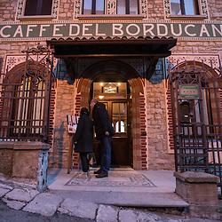 A couple checks the menu of the Caffè del Borducan in Santa Maria del Monte near Varese, Italy