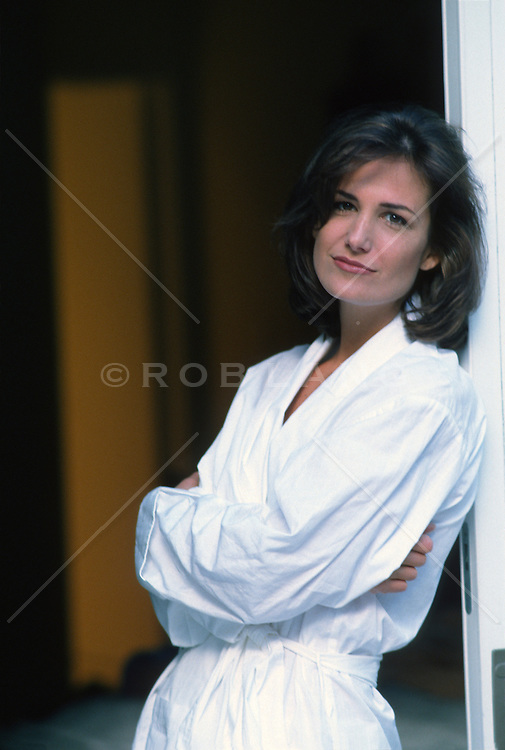 Woman in a white bathrobe leaning against a doorway