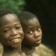 Africa, Liberia, Kpelle tribe: portrait of two boys, one smiling, one staring.