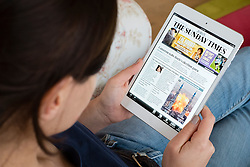 Woman reading digital edition of The Sunday Times on an iPad mini tablet computer