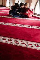 Finsbury Park Mosque, London, February 7th 2016. Whilst their parents watch Muslims at prayer during a tour of Finsbury Park Mosque, three little boys are absorbed by a game on a smartphone during the Visit My Mosque initiative by the Muslim Council of Britain to show non-Muslims &ldquo;how Muslims connect to God, connect to communities and to neighbours around them&rdquo;.<br /> . ///FOR LICENCING CONTACT: paul@pauldaveycreative.co.uk TEL:+44 (0) 7966 016 296 or +44 (0) 20 8969 6875. &copy;2015 Paul R Davey. All rights reserved.