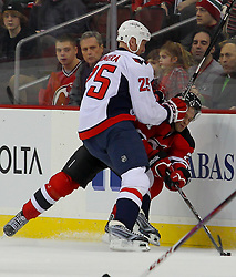 Jan 25, 2013; Newark, NJ, USA; Washington Capitals left wing Jason Chimera (25) hits New Jersey Devils left wing Mattias Tedenby (21) during the first period at the Prudential Center.