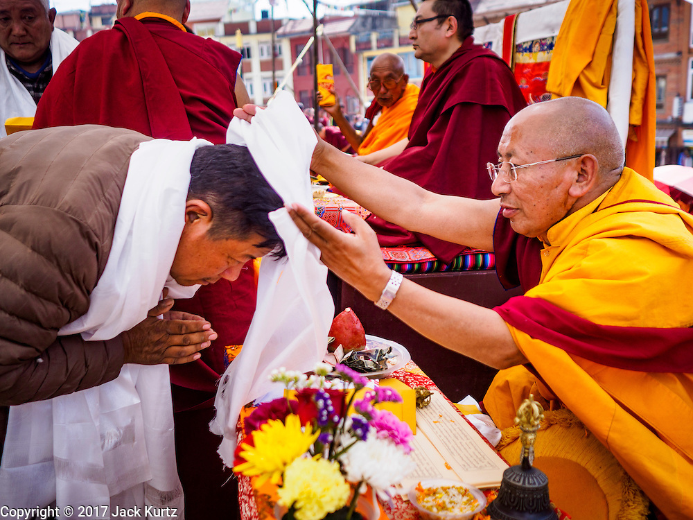 07 MARCH 2017 - KATHMANDU, NEPAL: A Buddhist monk places a prayer shawl around a lay person's neck during the consecration ceremony at Boudhanath Stupa. Boudhanath Stupa, the most important Buddhist site in Nepal and a popular tourist attraction, was consecrated Tuesday in a ceremony attended by thousands of Buddhist monks and Buddhist people from Nepal and Tibet. The stupa was badly damaged in the 2015 earthquake that devastated Nepal. The stupa, which reopened in November 2016, was repaired in about 18 months. The repair was financed by private donations raised by international Buddhist organizations.     PHOTO BY JACK KURTZ