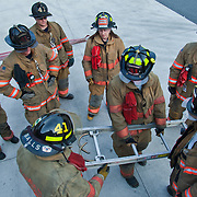 Lieutenant Maddy Cooper ( Bottom Right) observe Camden-Wyoming Fire fighters as they open hooks on top of a 24 foot ladder during ladder training Wednesday, July 6, 2011, in Camden-Wyoming Delaware.