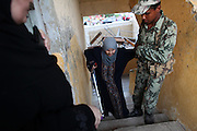 Egyptians security helps an elderly Egyptian woman up the stairs of a a polling station in   Cairo , Egypt May 23, 2012. Egyptians head to the polling stations throughout Egypt  Wednesday for an historic opportunity in which they will for the first time to pick their president in a wide open election that pits Islamists against men who served under deposed leader Hosni Mubarak.(Photo by Heidi Levine/Sipa Press).