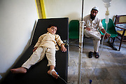 Abdul Sattar the father of Mohammad Ilyas, stands over his 3 year old son who's suffering from bloody diarrhoea. He'd been suffering for the last 3 days prior to being brought to the clinic and given intravenous fluids...Qambar Clinic on the outskirts of Mingora in the SWAT Valley is supported by Save the Children. The resident medical doctor is Dr Ikram who was the first Doctor to return to the clinic since the Taliban were driven out by government forces in 2009...Dr Ikram sees approx. 50 people per day with flooding/water related illnesses and symptoms such as diarrhoea, vomiting, high fever, dysentery, dehydration, skin diseases and upper respiratory infections...Dr Ikrams medical opinion is that many of the illnesses are related to ice. During the hot weather, families and children in particular buy ice to cool don in the hot climate, however, it is suspected that the water used to produce the ice is drawn from contaminated sources...The majority of the children seen are between the ages of 2-10 years of age. At the moment the clinic estimates it is receiving 1-2 cases per day of suspected Malaria, but without an in house testing laboratory, they cant confirm suspected cases of Malaria or Cholera. Due to the increase in patients attending the clinic as a result of the flooding, they are now running short on some medicines...Patients prefer to visit this Save the Children sponsored clinic over the government hospitals as they trust the NGO employed doctors more than those employed by the government, and medicines will be more readily available and the NGO clinic...The clinic offers free medical consultations, medicines and free hygiene kits. During the flooding, the clinic has operated a 7 day week, from 8am until 14.00pm..