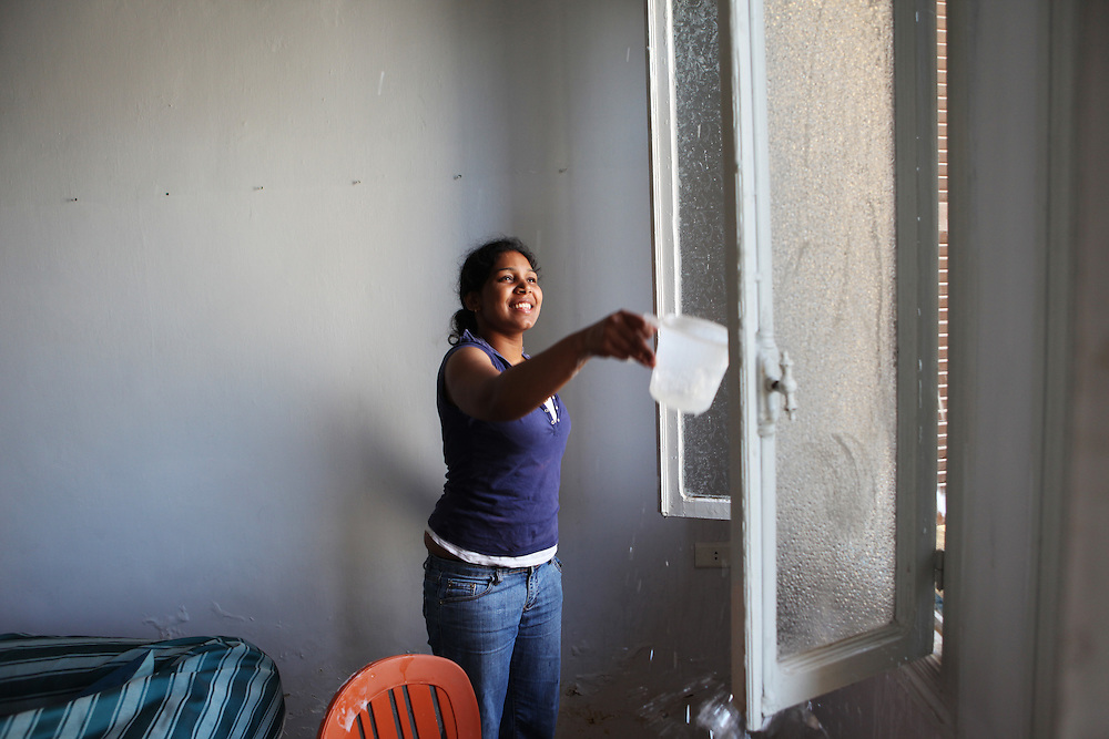 A Sri Lankan woman throws soapy water on windows careful not to  get any on her clothes.