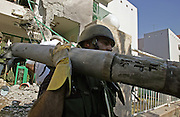 An Israeli police sapper carries away a rocket that slammed into an apartment building in the northern Israeli town of Kiryat Shmona August 5,2006 damaging the building . Israel was once again hit by a barrage of rockets fired by Hizbollah guerrillas in Lebanon.