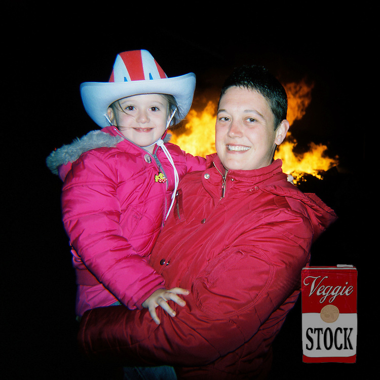 A mother and child pose for a photo next to a bonfire in Belfast, Northern Ireland, July 2008. The bonfires are built in preparation for the annual 12th July celebrations, which commemorate the defeat of James Stuart at the Battle of the Boyne in 1690.