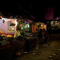 A couple friends engage in horseplay in the vegetable market one night, Kargil