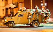 An armored vehicle shuttles police officers to the scene of civil unrest as protesters became violent following the death of Freddie Gray.  Bryan Woolston / For the Daily Mail.