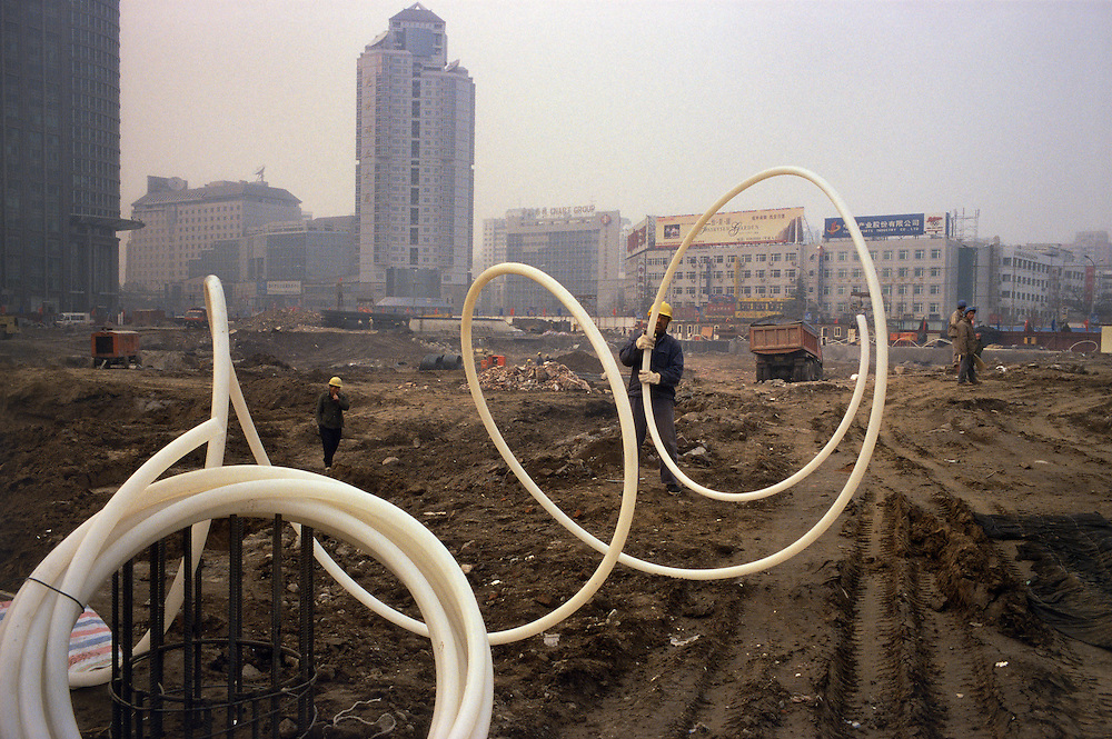 Migrant labourers from Henan Province at work on a downtown construction site, in a pollution haze that closed the airport. The site was formerly occupied by hutong housing...From China [sur]real © Mark Henley..