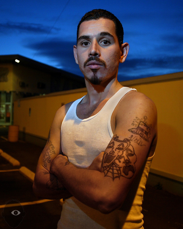 "Mark DeLeon who is with the Southside Loco Mafia Varios. He wears many tattoos including t a classic one denoting the gang philosophy of laugh now, cry later (bottom). Also a Cholo hat with his nickname ""Panther"" and various affiliations."