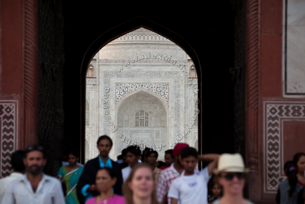 Visitors are walking through the Great Gate, heading home after a day at the Taj Mahal complex, in Agra.