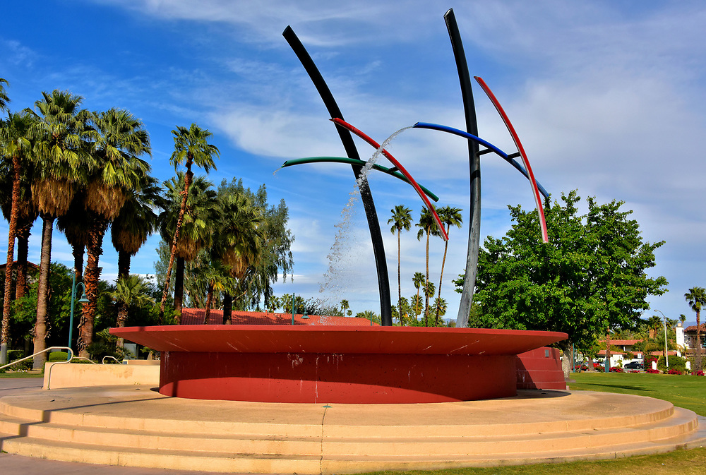 Rainmaker Fountain in Palm Springs, California<br /> During the summer months, thermometers in Palm Springs often push beyond 110&deg; F. When it is that hot, parents will often bring their children to Frances Stevens Park to experience &ldquo;The Rainmaker&rdquo; not as a form of outdoor art but with the hopes a slight breeze will send cooling mists from the four moving arms. The kinetic sculpture by David Morris was created in 2000.
