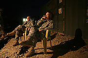 Major Rebecca Schieble, 28 (right), and a mother of 5 is  an ICU nurse at the Combat Support Hospital at Camp Speicher smokes cigars after dinner with ICU nurse Captain Sarah Bivens, 43, a mother of three children and a grandmother  at US Base Camp Speicher in Iraq.  Both women work and live together . (Photo by Heidi Levine /Sipa Press).