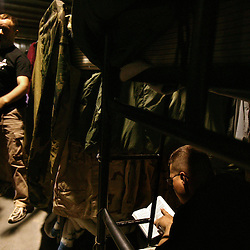 Sgt. Thomas Wingfield, right, from the 724th Transportation Company, reads while waiting to go back to the United States, Kuwait, Feb. 7, 2005. A member of their unit, Army Spc. Keith Matt Maupin, was taken hostage. He is the only US soldier that is listed MIA from this war.