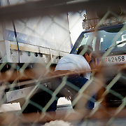An Afghan migrant attempts to smuggle himself under a truck headed for Italy, after scaling the fence of the international port in Patras, Greece, the gateway out of Greece allowing migrants to travel further in the Schengen zone.