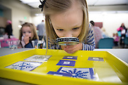"Lila Kelly, 5, of south Des Moines, inspects snowflakes with a magnifying glass Tuesday, Dec. 23, 2014, during a ""Frozen"" party, themed on the movie, at the Franklin Avenue Library in Des Moines."