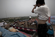 Villagers move their belongings onto trucks in preparations for relocation to neigbouring Hui county to make way for the colossal South-to-North Water Diversion (SNWD) project in Xichuan county of Henan Province in China on 28 June 2010. The central route, which will raise the height of the Danjiangkou reservoir dam from 162 meters to 176.6 meters, requires the relocation of 330,000 people in Henan and Hubei provinces. Xichuan, a remote, mountainous region inaccessible by railway, is home to 162,000 would-be SNWD migrants, the most anywhere. The SNWD project, the largest known water diversion project, was started in 1952 to solve the country's chronic water shortages and involves creating three routes to channel 44.8 billion cu m of water from southern China to the northern areas. As part of the project's central route, affecting Henan and Hubei provinces, water from the Danjiangkou Dam reservoir will be diverted to Beijing.