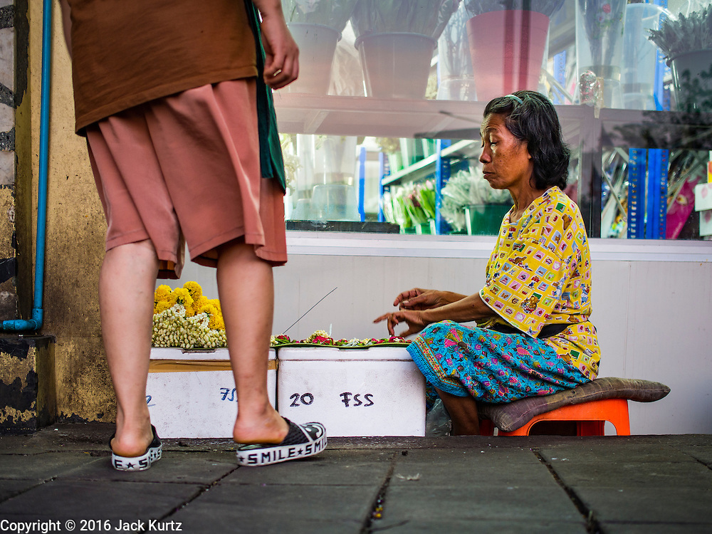 29 FEBRUARY 2016 - BANGKOK, THAILAND: A sidewalk vendor sells flower garlands from the window box of a florist shop in the Bangkok flower market. She used to sell from a table against the wall to the left of where she's sitting. Many of the sidewalk vendors around Pak Khlong Talat, the Bangkok flower market, closed their stalls Monday. As a part of the military government sponsored initiative to clean up Bangkok, city officials announced new rules for the sidewalk vendors that shortened their hours and changed the regulations they worked under. Some vendors said the new rules were confusing and too limiting and most vendors chose to close Monday rather than risk fines and penalties. Many hope to reopen when the situation is clarified.    PHOTO BY JACK KURTZ