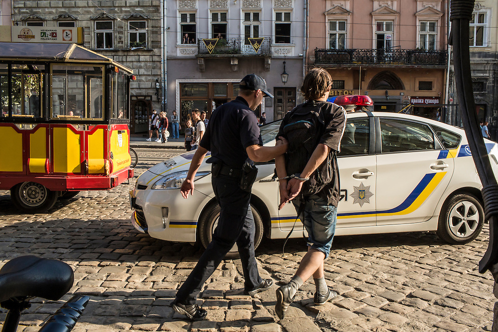 LVIV, UKRAINE - SEPTEMBER 16, 2015: A member of the new Lviv police arrests Vladimir, 26, after he was found intoxicated and sleeping in the city's central square and then swore at police officers in Lviv, Ukraine. In an effort to reform the notoriously corrupt Ukrainian police force, an entirely new force has been established in several cities, including Kiev and Lviv, with a primary focus on patrolling the streets. CREDIT: Brendan Hoffman for The New York Times